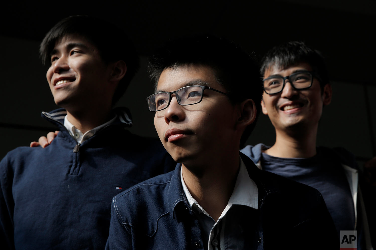 From left, Hong Kong's young democracy leaders Lester Shum, Joshua Wong and Alex Chow pose for photographers in front of the High Court in Hong Kong, Thursday, Dec. 7, 2017. Hong Kong's young democracy leader Joshua Wong faces a possible new prison sentence in a case stemming from 2014 protests in the semiautonomous Chinese city. He's among a group of activists awaiting sentencing Thursday afternoon following their convictions months earlier. (AP Photo/Kin Cheung)