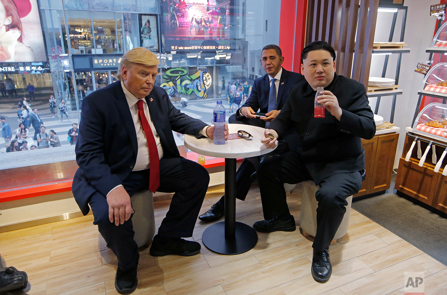 North Korean leader Kim Jong Un, former U.S. President Barack Obama and U.S. President Donald Trump impersonators, from right, Howard, Reggie Brown and Dennis Alan, take rest at a cafe as they promote the Hong Kong Rugby Sevens in Hong Kong, Friday, April 7, 2017.  (AP Photo/Kin Cheung)