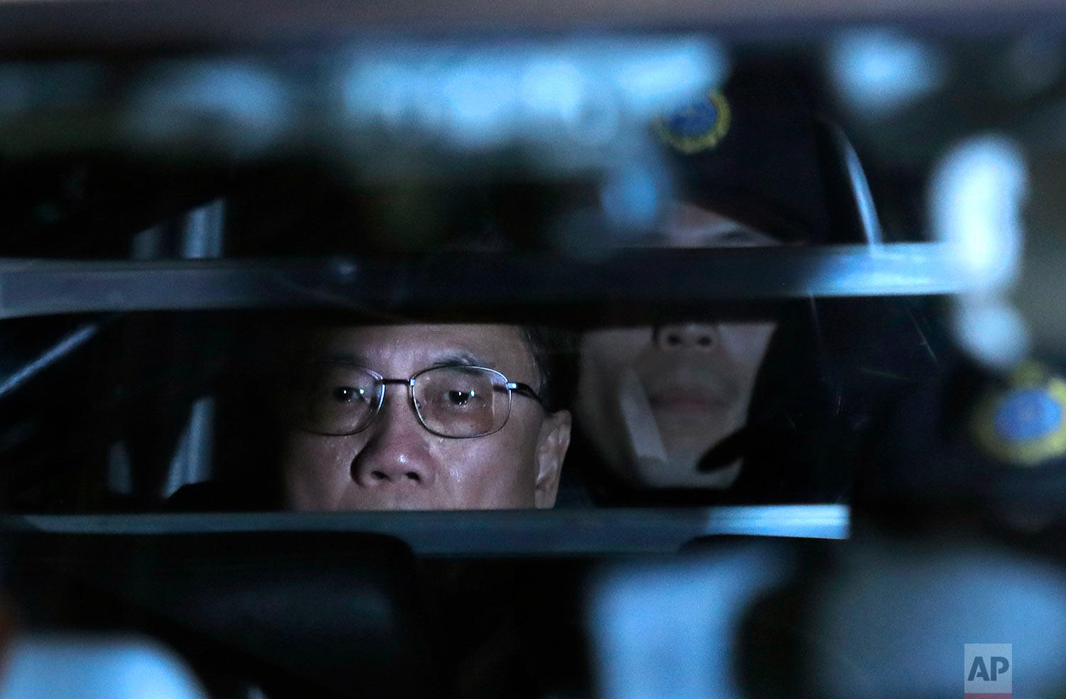 In this Monday, Feb. 20, 2017 photo, Donald Tsang, center, former leader of Hong Kong, is escorted in a prison bus leaving the high court after sentencing and mitigation after his conviction last week for misconduct in public office, in Hong Kong. Tsang was found guilty by a jury of one count of misconduct in public office over a luxury apartment in mainland China, making him the highest ranking current or former official to be convicted for corruption in the Asian financial hub. (AP Photo/Vincent Yu, File)