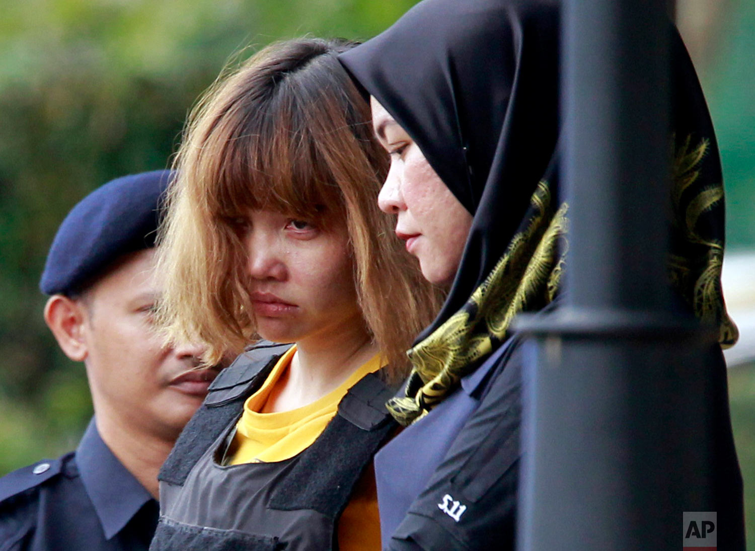 In this March 1, 2017, photo, Vietnamese Doan Thi Huong, center, a suspect in the ongoing investigation into the assassination of Kim Jong Nam, is escorted by police from Sepang court in Sepang, Malaysia. Appearing calm and solemn, two young women accused of smearing VX nerve agent on Kim Jong Nam, the estranged half brother of North Korea's leader, were charged with murder. (AP Photo/Daniel Chan)