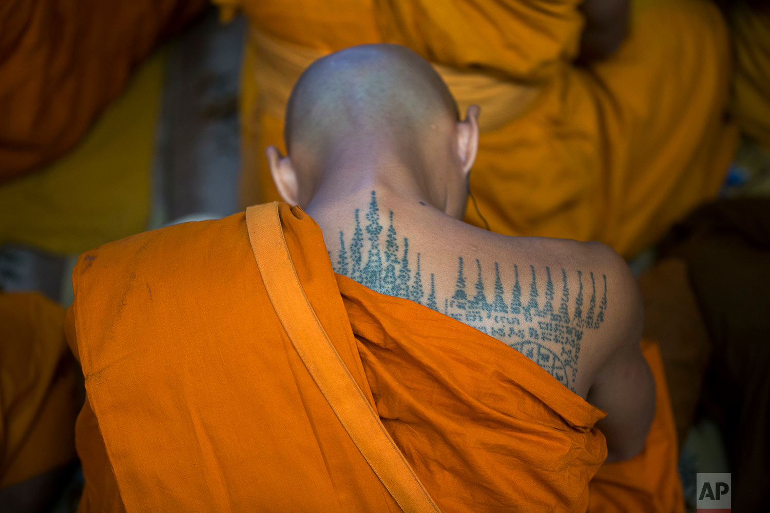 A Thai Buddhist monk with a tattooed back listens to the Tibetan spiritual leader Dalai Lama during a religious talk at the Tsuglagkhang temple in Dharmsala, India, Wednesday, June 7, 2017. Each year the Tibetan leader talks to young Tibetans on Buddhist philosophy and selected texts. The three-day talk ended Wednesday. (AP Photo/Ashwini Bhatia)