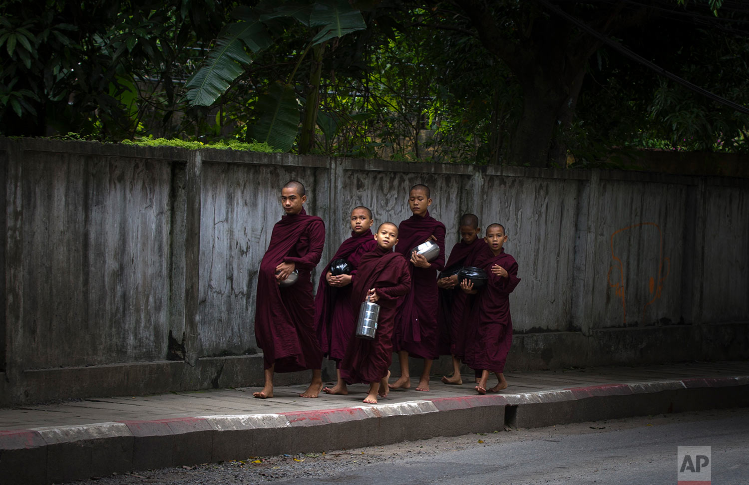 """In this Friday, June 16, 2017, file photo, a group of Myanmar Buddhist monks walk to collect their morning """"alms"""" or offerings in Yangon, Myanmar. (AP Photo/Thein Zaw, File)"""