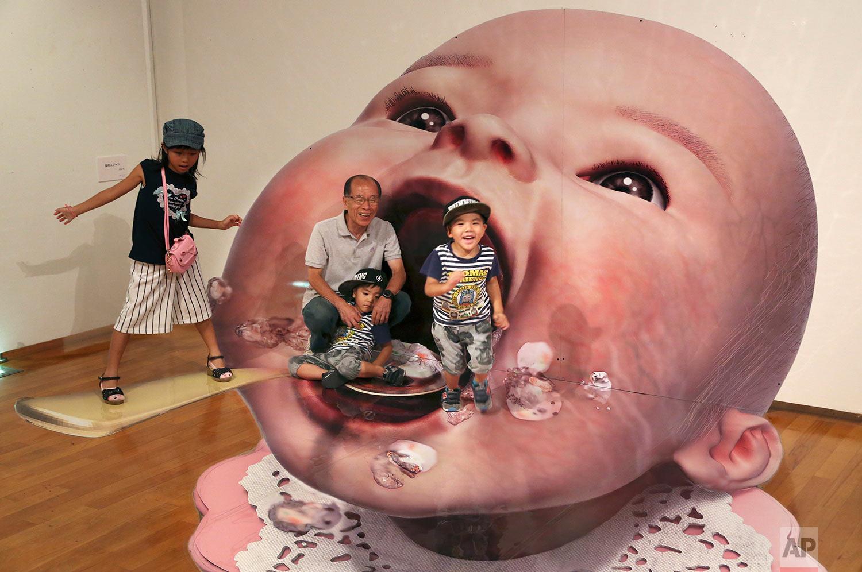 In this Saturday, Aug. 5, 2017, photo, visitors pose for a photo with a 3D image at an art exhibition by Japanese artist Masashi Hattori in Kawasaki, near Tokyo. (AP Photo/Koji Sasahara)