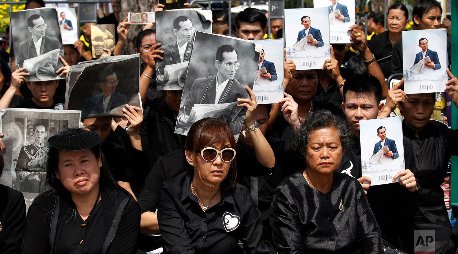 Mourners hold aloft the portraits of late Thai King Bhumibol Adulyadej during his funeral procession and royal cremation ceremony, in Bangkok, Thailand, Thursday, Oct. 26, 2017. Tearful Thais clad in black mourned on Bangkok's streets or at viewing areas around the nation Thursday as elaborate funeral ceremonies steeped in centuries of royal tradition were held for King Bhumibol following a year of mourning. (AP Photo/Sakchai Lalit)