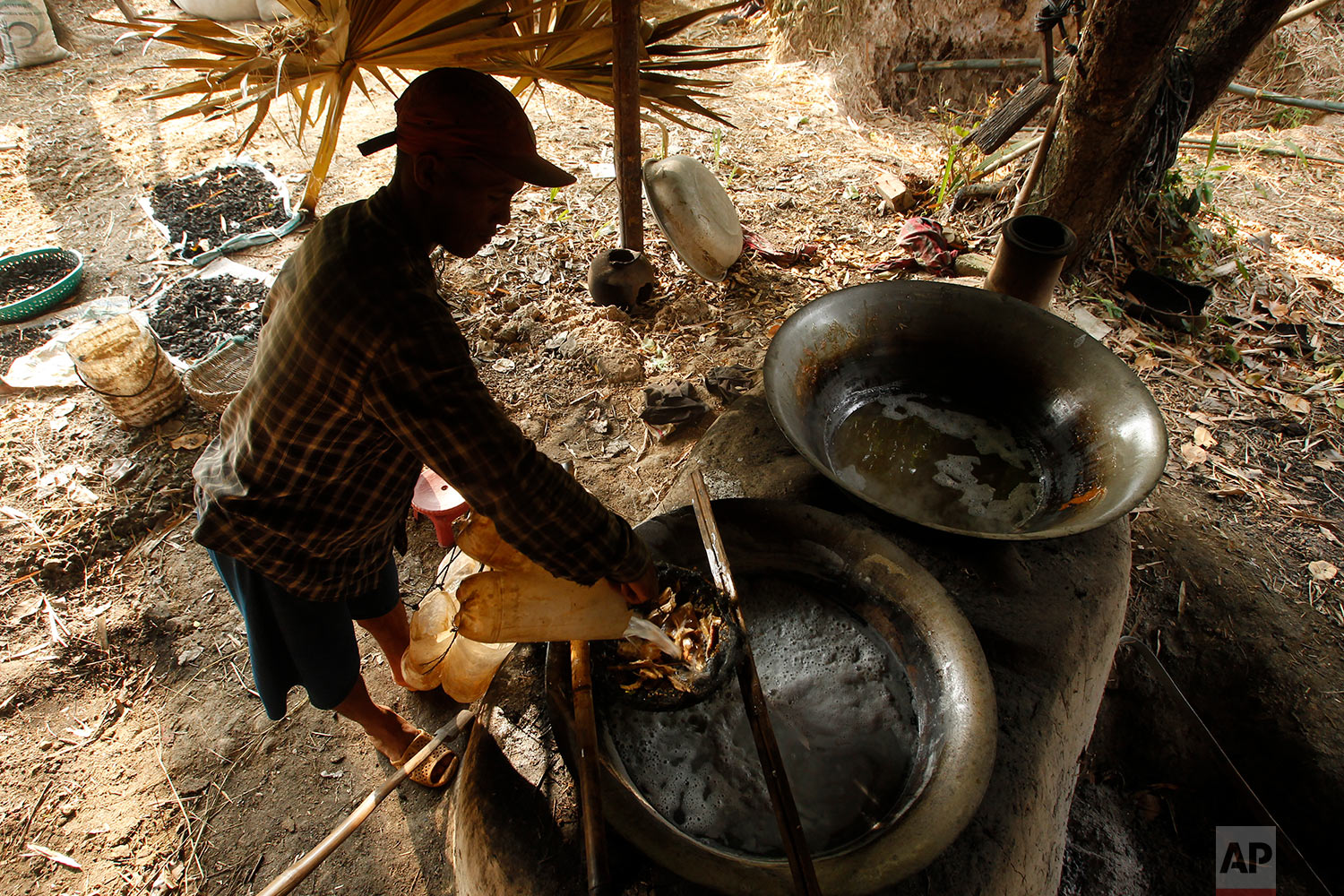 A man prepares palm sugar from the palm juice he collected from trees during its harvesting season at Samroang village on the north side of Phnom Penh, Cambodia, Thursday, Dec. 14, 2017. Some villagers earn up to $7 a day collecting palm juice as part of their daily income. (AP Photo/Heng Sinith)