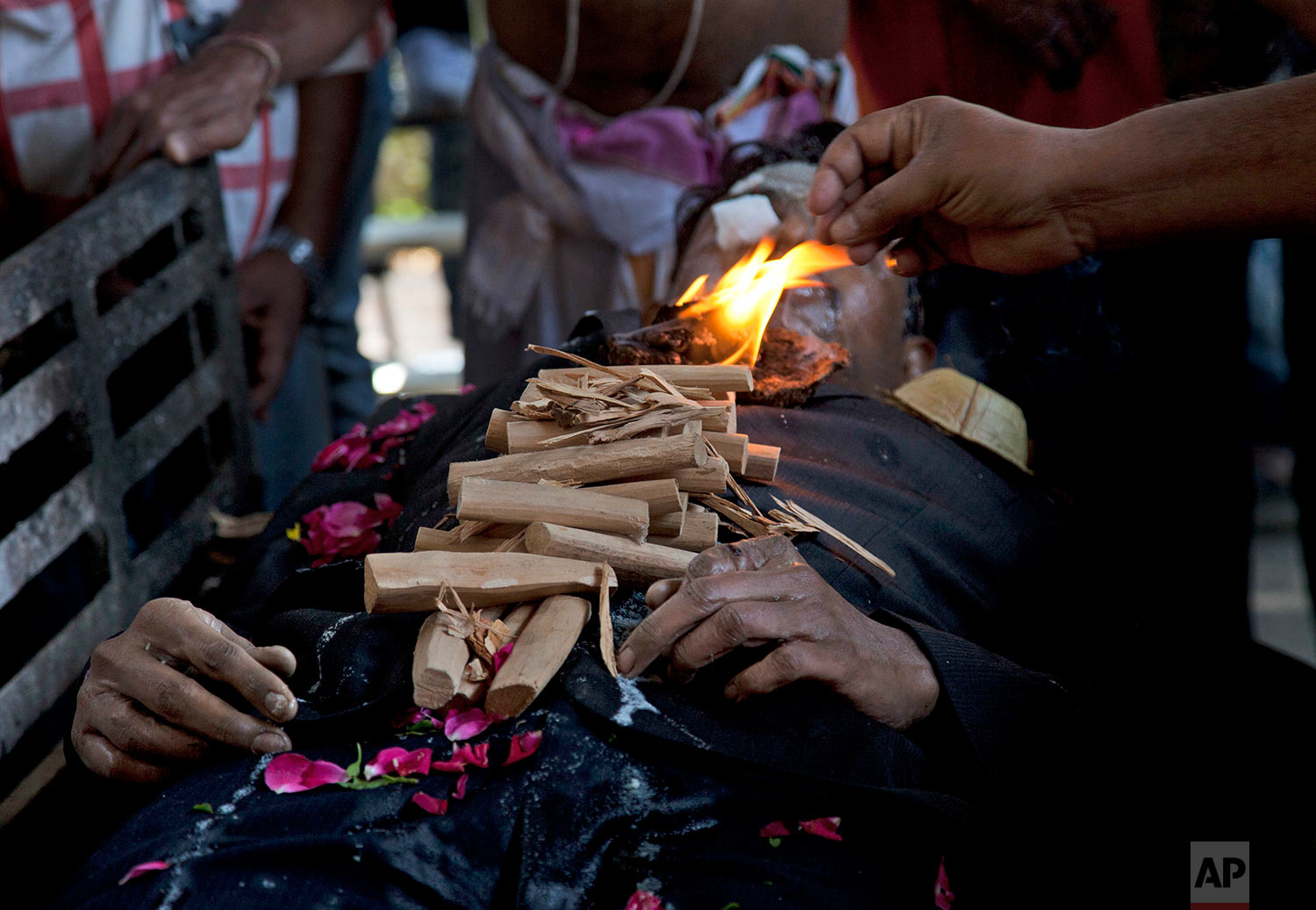 """A family member performs rituals over the body of Srinivas Kuchibhotla, a 32-year-old engineer who was killed in an apparently racially motivated shooting in a crowded Kansas bar, at a crematorium in Hyderabad, India, Tuesday, Feb.28, 2017. According to witnesses, the gunman yelled """"get out of my country"""" at Kuchibhotla and Alok Madasani before he opened fire at Austin's Bar and Grill in Olathe, Kansas, a suburb of Kansas City, on Wednesday evening. Both men had come to the U.S. from India to study and worked as engineers at GPS-maker Garmin. (AP Photo/Mahesh Kumar A.)"""