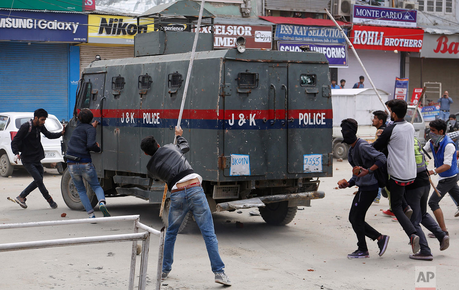 Kashmiri students and other protesters attack an Indian police vehicle as they clash in Srinagar, Indian controlled Kashmir, Monday, April 24, 2017. Tensions between Kashmiri students and Indian law enforcement have escalated since April 15, when government forces raided a college in Pulwama, about 30 kilometers (19 miles) south of Srinagar, to scare anti-India activists. (AP Photo/Mukhtar Khan)