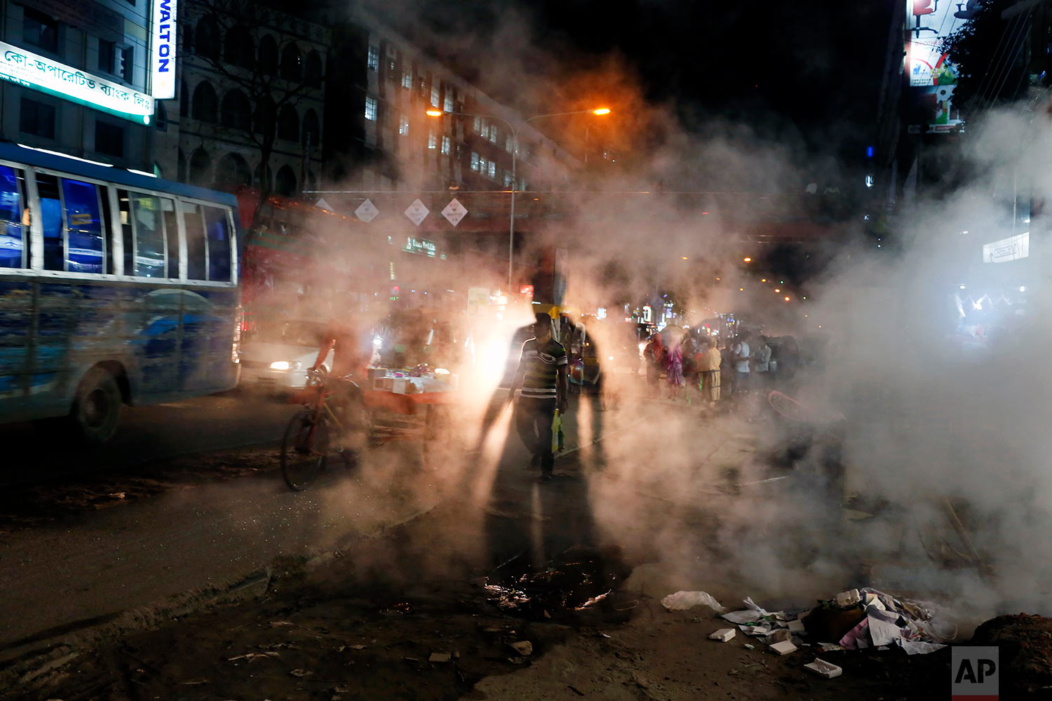 In this Wednesday, April 26, 2017 photo, a Bangladeshi man is silhouetted against the headlight of a car as he walks past smoke rising from a manhole on a hot summer evening in Dhaka, Bangladesh. (AP Photo/ A. M. Ahad)