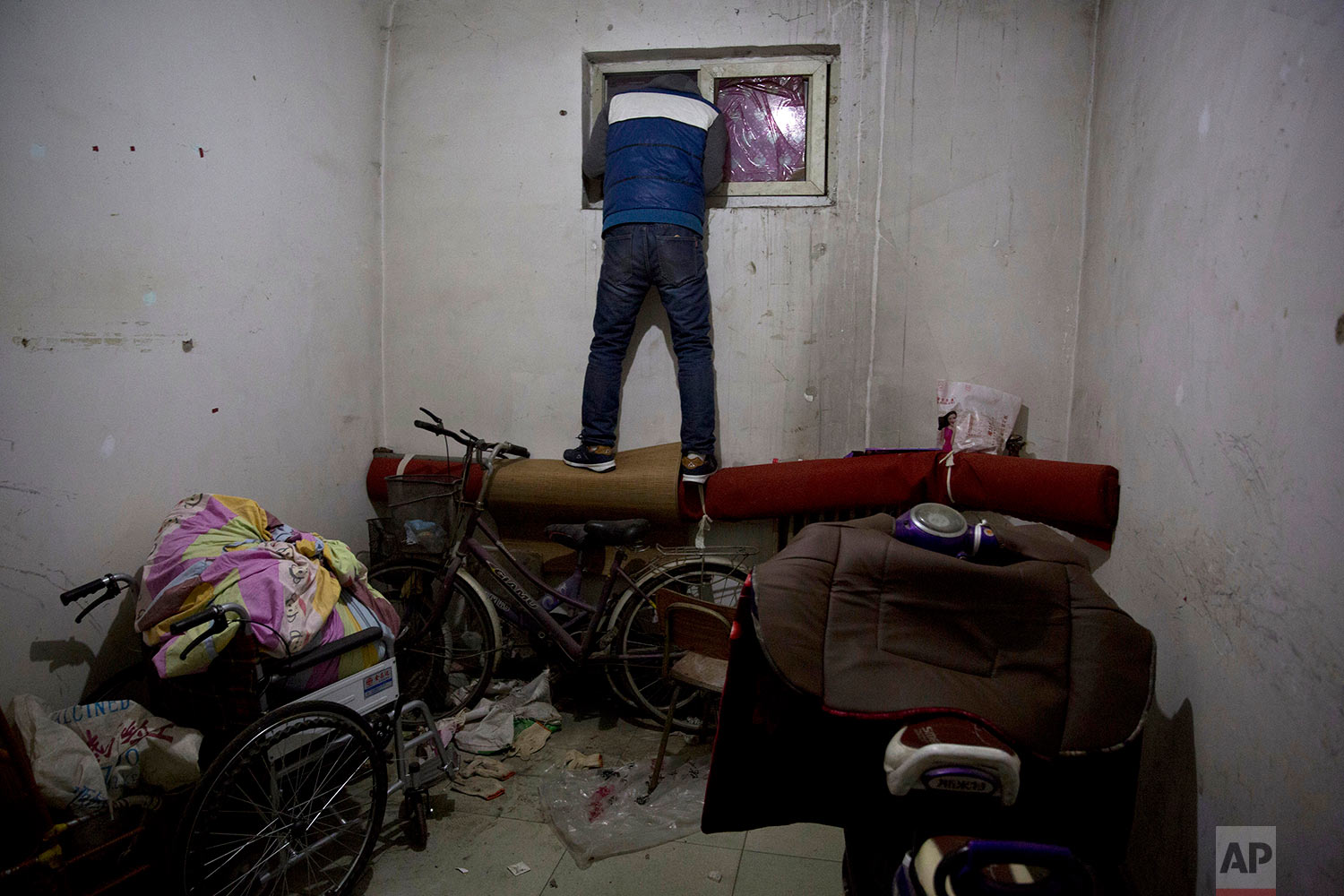 In this Nov. 27, 2017, photo, a man looks outside the window of an apartment where migrant workers stayed in the outskirts of Beijing. Authorities in Beijing have been evicting domestic migrant workers from the capital in droves, triggering a public outcry over the harsh treatment of people the city depends on to build their skyscrapers, care for their children and take on other lowly-paid work. (AP Photo/Ng Han Guan)
