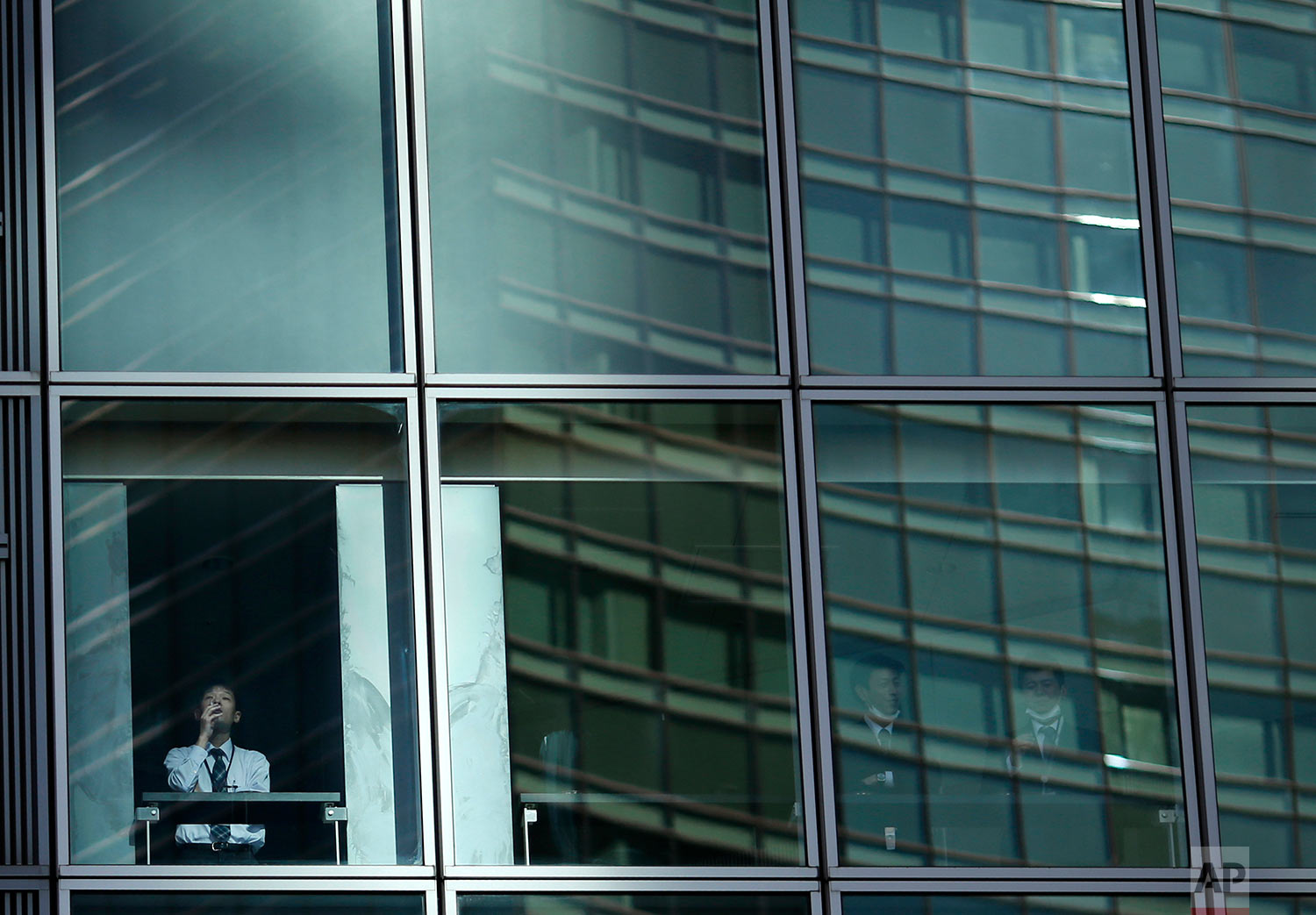 In this Wednesday, Jan. 11, 2017 photo, an employee smokes at the window of a high-rise building in a Tokyo's business area. (AP Photo/Shuji Kajiyama)