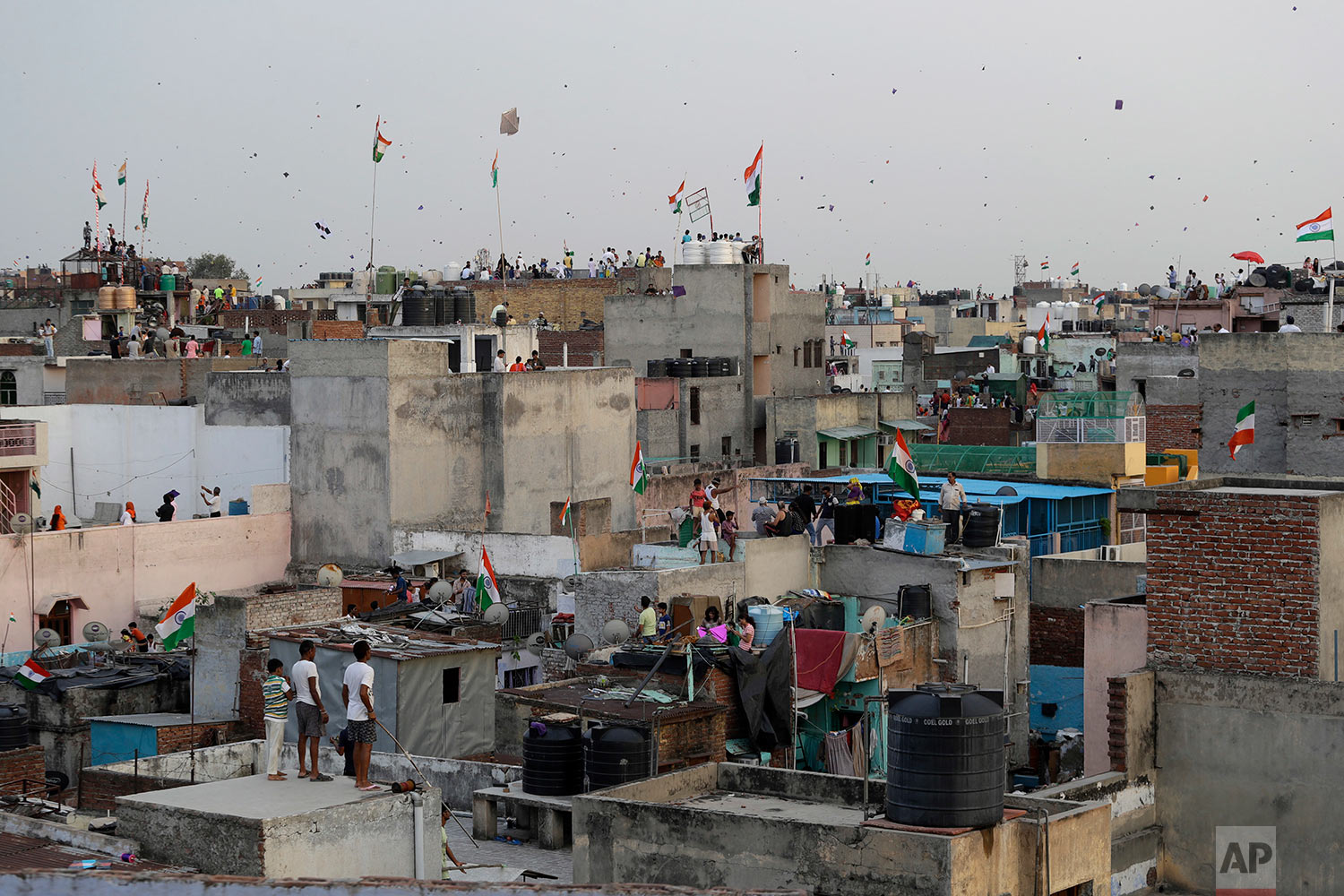 In this Tuesday, Aug. 15, 2017 photo, Indians fly kites on rooftops during Independence Day celebrations in the old quarters of New Delhi, India. The annual tradition of flying kites over the Indian capital on Independence Day takes a painful toll on birds that fall victim to their razor-sharp strings. It happens mostly to pigeons but also to crows, eagles and parrots. (AP Photo/Tsering Topgyal)