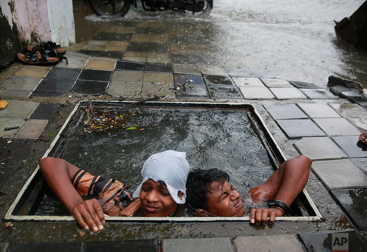 Municipal workers try to retrieve the lid of a manhole to prevent pedestrians from falling in, in Mumbai, India, Wednesday, Sept. 20, 2017. Incessant rainfall in India's commercial capital has affected air and rail traffic, and schools and colleges remained shut for the day. (AP Photo/Rafiq Maqbool)