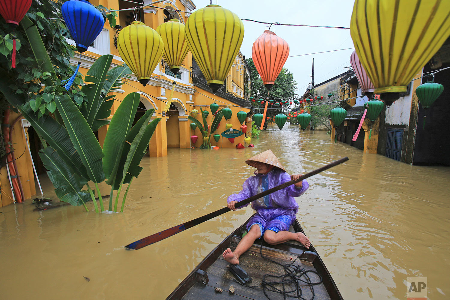 In this Monday, Nov. 6, 2017, photo, Nguyen Thi Vui paddles her boat in the flooded streets of Hoi An, Vietnam. A powerful typhoon that rocked Vietnam has killed dozens of people and caused extensive damage to the country's south-central region ahead of the APEC summit that will draw leaders from around the world, the government said Monday. (AP Photo/Hau Dinh)