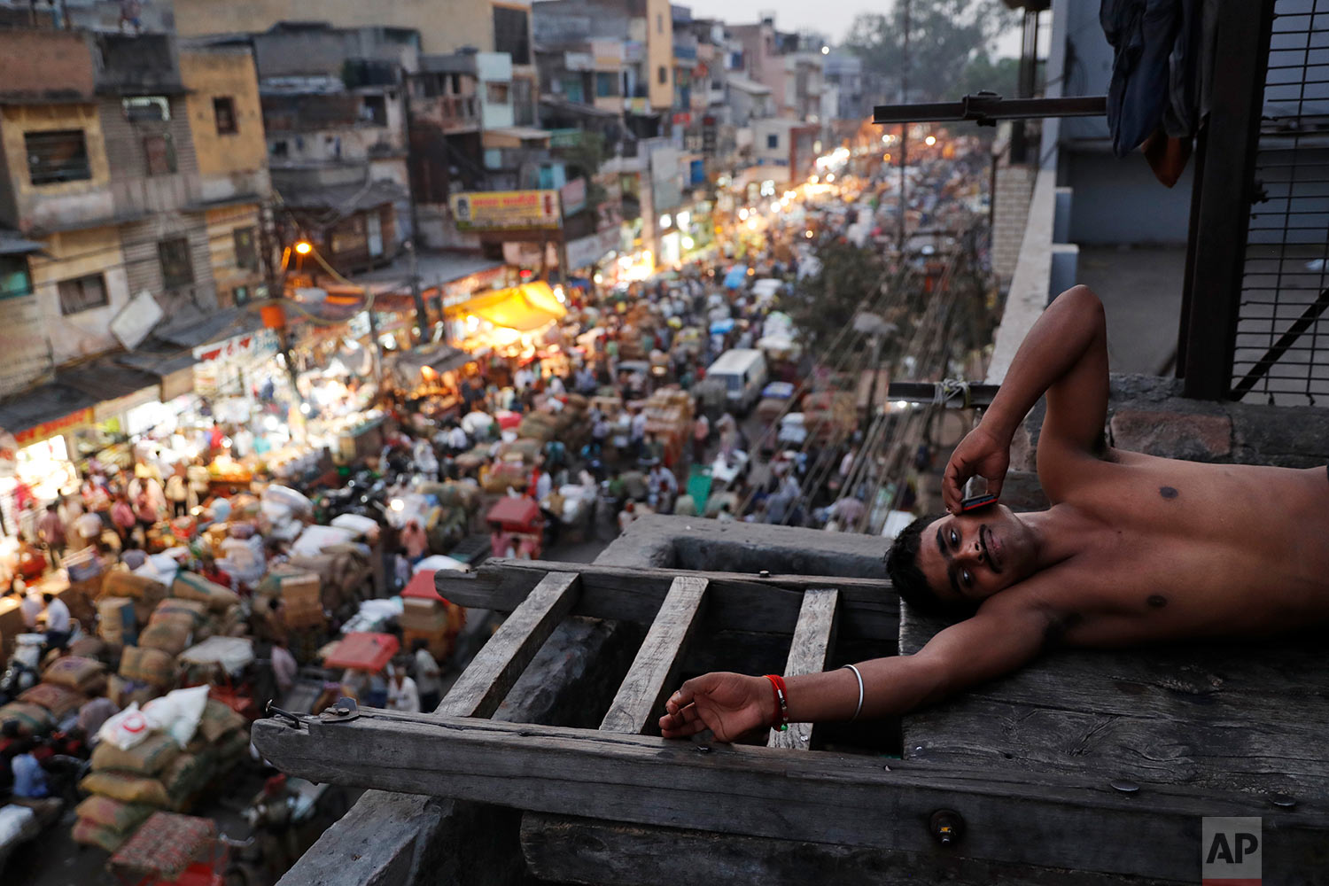 An Indian laborer rests after work as push carts and cycle rickshaws make their way through a crowded street at the old quarters of New Delhi, India, Tuesday, Oct. 10, 2017. (AP Photo/Tsering Topgyal)