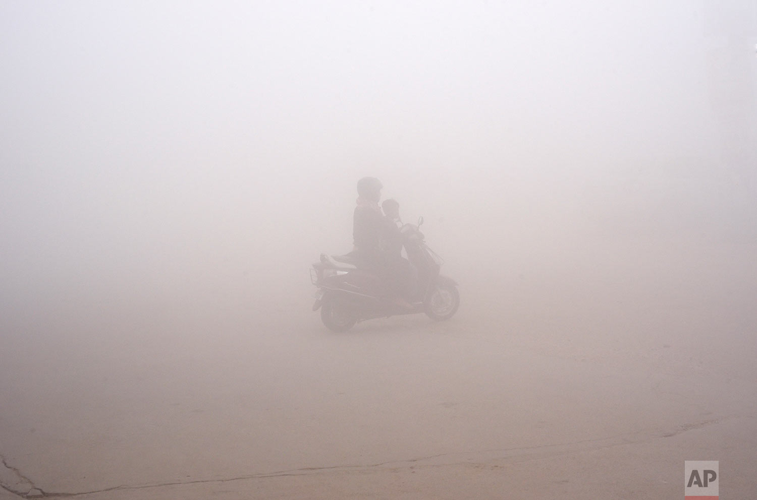 In this Thursday, Nov. 9, 2017, photo, a woman drives a scooter through the morning fog to drop off a child at school in Greater Noida, near New Delhi, India. A thick gray haze has enveloped India's capital region as air pollution hit hazardous levels. As winter approaches, a thick, soupy smog routinely envelops most parts of northern India, caused by dust, the burning of crops, emissions from factories and the burning of coal and piles of garbage as the poor try to keep warm. (AP Photo/R S Iyer)