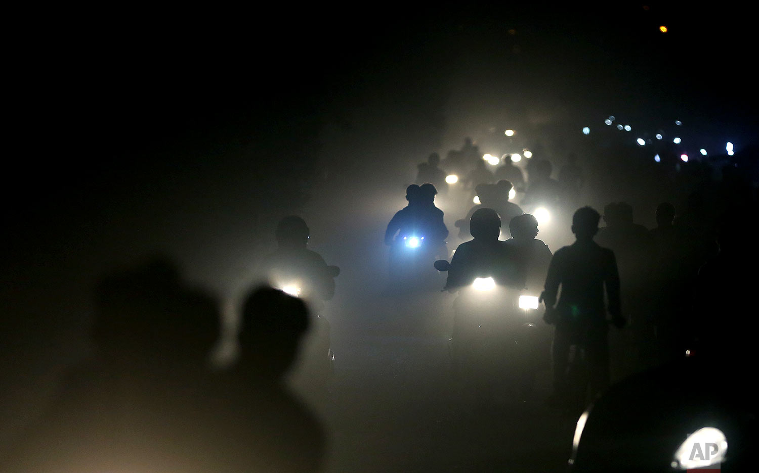 Indian motorists ride past a thick blanket of smog and dust on the outskirts of New Delhi, India, Friday, Nov. 10, 2017.  Thick smog has constricted India's capital this week, smudging landmarks from view and angering residents. Many are frustrated at the lack of meaningful action by authorities. The air was the worst it has been all year in New Delhi, with microscopic particles that can affect breathing and health spiking, at times, to 75 times the level considered safe by the World Health Organization. (AP Photo/Altaf Qadri)