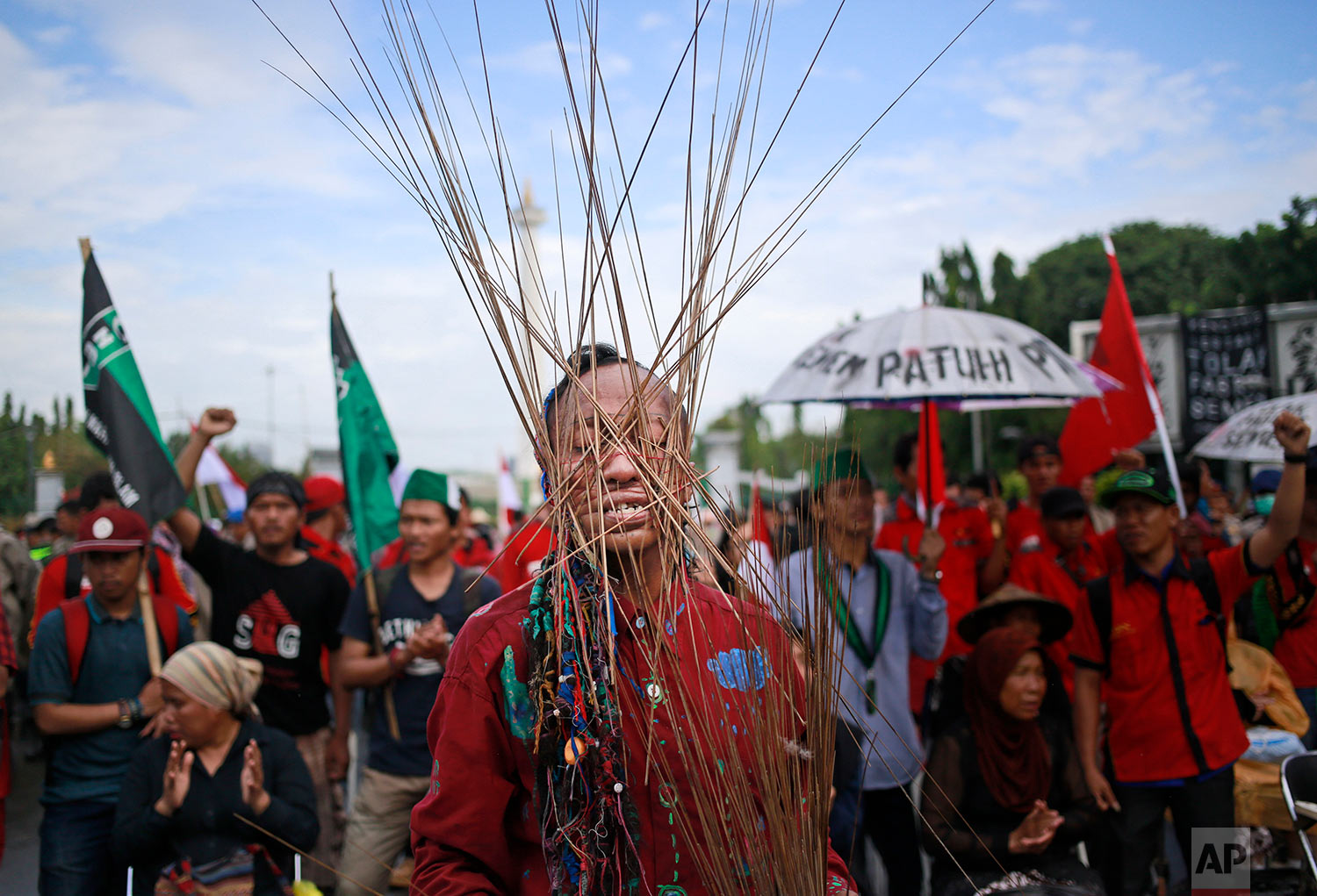 In this March 20, 2017 photo, an activist has skewers wrapped around his head with rubber bands during a rally against the operation of a cement factory in Kendeng, West Java, outside the presidential palace in Jakarta, Indonesia. Kendeng farmers have battled against plans for the factory for years, saying it could taint their water. The factory is now more or less complete and the owner, state-owned PT Semen Indonesia, has said it would create jobs and boost the local economy. (AP Photo/Dita Alangkara)