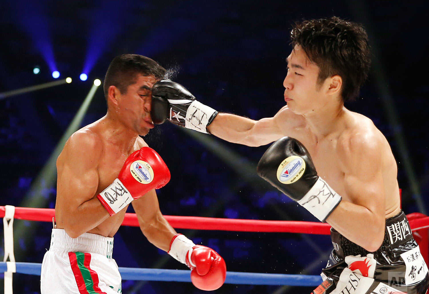 In this Saturday, May 20, 2017, photo, Japan's Shiro Ken, right, lands a right on the face of Mexican champion Ganigan Lopez in the third round of their WBC light flyweight boxing world title match in Tokyo, Saturday, May 20, 2017. Ken won the title by a 2-0 decision. (AP Photo/Toru Takahashi)