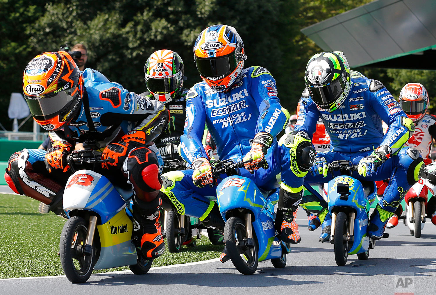 In this Tuesday, Oct. 10, 2017, photo, MotoGP rider Tito Rabat, left, of Spain steers his mini electric motorcycle as he leads the pack of riders during a fan event at the Twin Ring Motegi circuit ahead of the MotoGP Japanese Motorcycle Grand Prix in Motegi, north of Tokyo. (AP Photo/Shizuo Kambayashi)