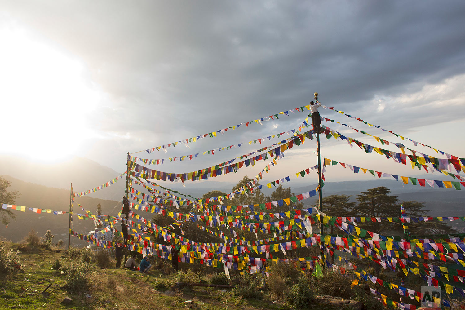 Exile Tibetans climb high on poles to tie multicolored flags with Buddhist prayers printed on them on the third day of the Tibetan New Year called 'Losar' in Dharmsala, India, Wednesday, March 1, 2017. Tibetans believe that the prayer flags representing the five elements: earth, fire, sky, water and wind, spread prayers on wind. (AP Photo/Ashwini Bhatia)