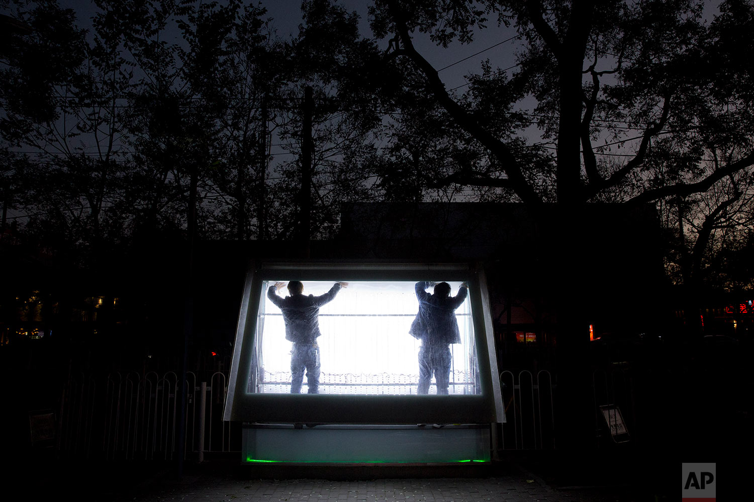 Workers prepare to install advertisements in a display case on the streets of Beijing, China, Wednesday, Nov. 22, 2017. Digital advertisement continues to grow in China, one of the world's largest ad market, where consumers embrace mobile technology and increasingly spend more time online. (AP Photo/Ng Han Guan)