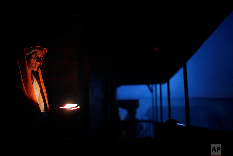 A Hindu holy woman lights an oil lamp during Shivaratri festival in Kathmandu, Nepal, Friday, Feb. 24, 2017. Shivaratri, or the night of Shiva, is dedicated to the worship of Lord Shiva, the Hindu god of death and destruction. (AP Photo/Niranjan Shrestha)