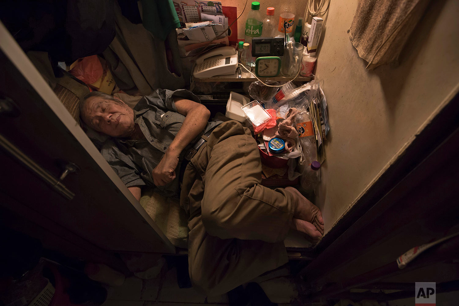 """In this Thursday, March 28, 2017 photo, Cheung Chi-fong, 80, sleeps in his tiny """"coffin home"""" where he cannot stretch out his legs in Hong Kong. In wealthy Hong Kong, there's a dark side to a housing boom, with hundreds of thousands of people forced to live in partitioned shoebox apartments, """"coffin homes"""" and other """"inadequate housing.(AP Photo/Kin Cheung)"""