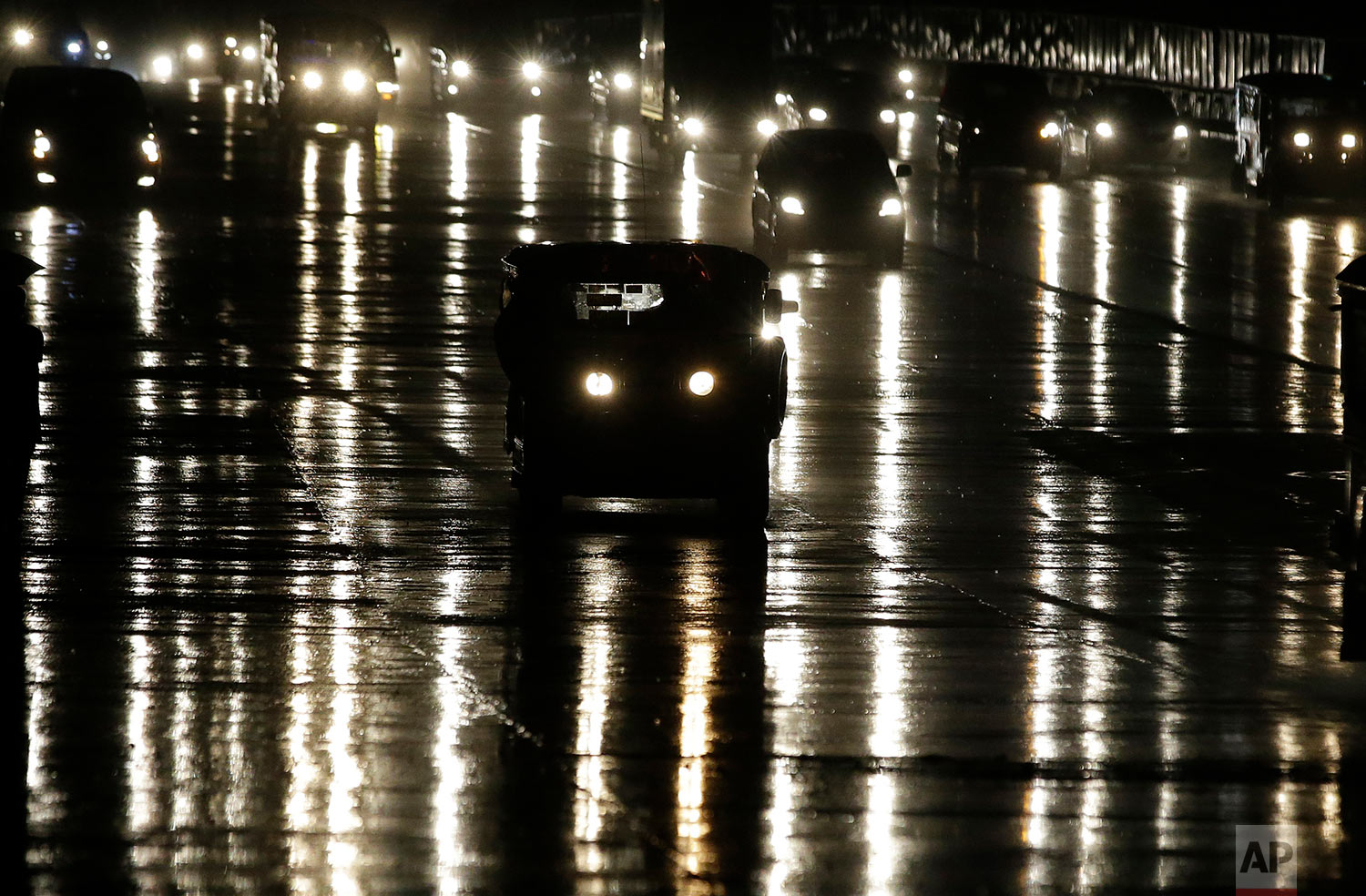 """A passenger jeepney travels along a wet road during rains in metropolitan Manila, Philippines on Tuesday, Sept. 26, 2017. Passenger jeepneys, often dubbed as the """"King of the Road"""" in the Philippines now faces new challenges as the government will soon implement the Public Utility Vehicle modernization program which aims to rid them of their aging diesel engines and also add more safety modifications, including public wifi and on-board CCTV. The program will affect some 600,000 Filipino drivers in the country. (AP Photo/Aaron Favila)"""