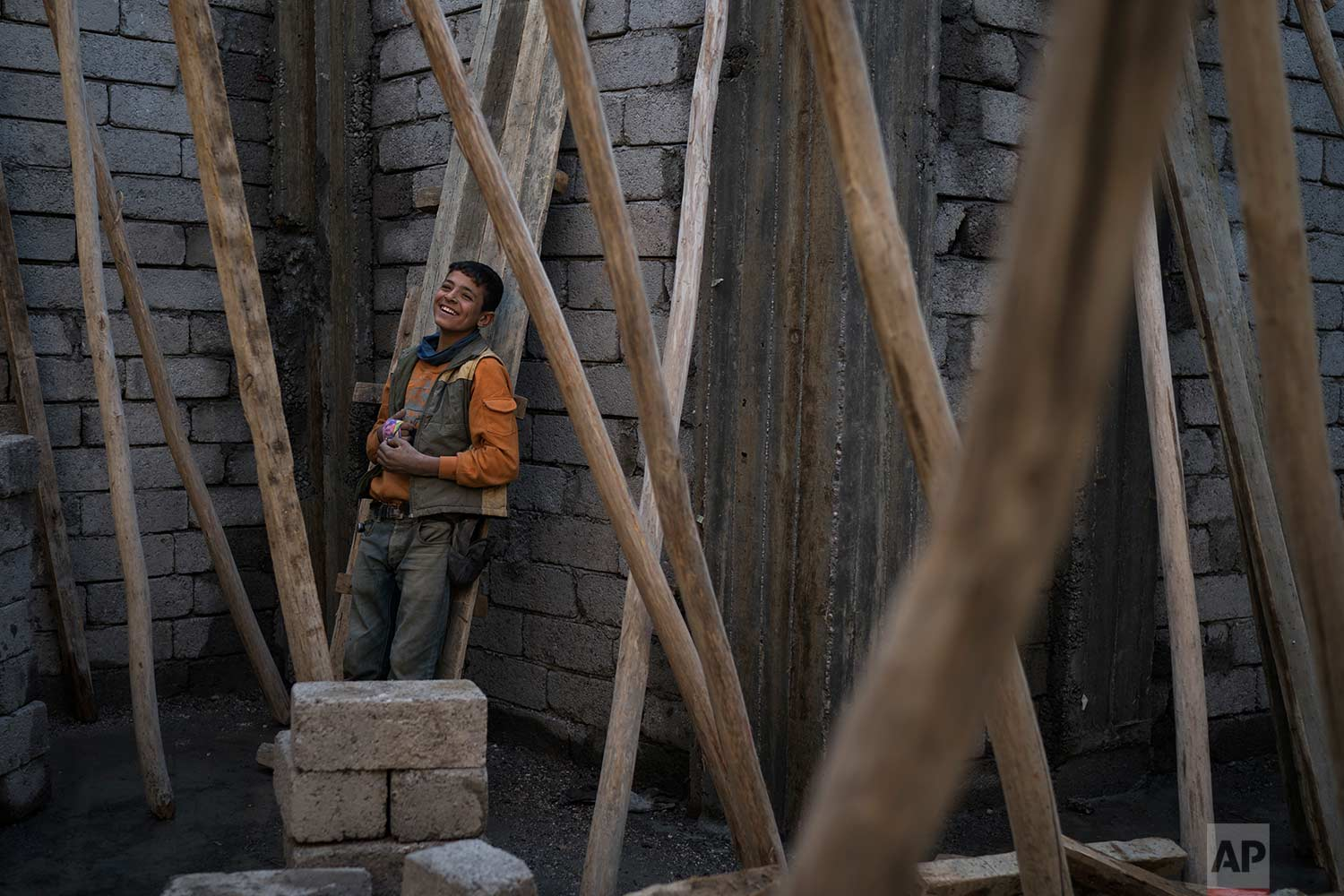 In this Nov. 14, 2017 photo, a young construction worker smiles during a break as he rebuilds a destroyed shop in the Old City of Mosul, Iraq. (AP Photo/Felipe Dana)