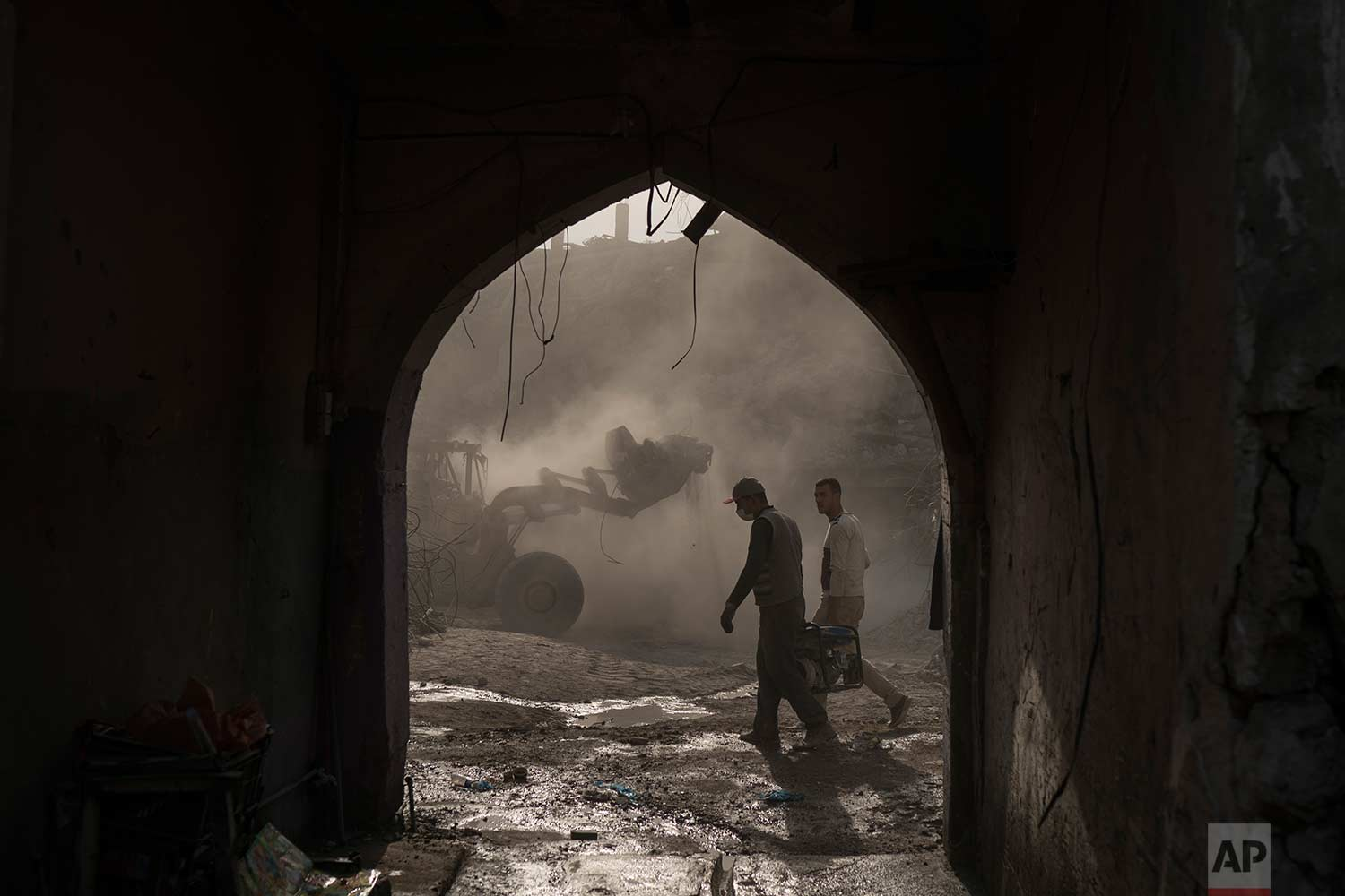 In this Nov. 18, 2017 photo, construction workers carry a generator as a bulldozer removes debris from destroyed shops in the Old City of Mosul, Iraq. Along the neighborhood's gutted roads, a handful of people are beginning to rebuild but the task ahead will take years - and billions of dollars. (AP Photo/Felipe Dana)