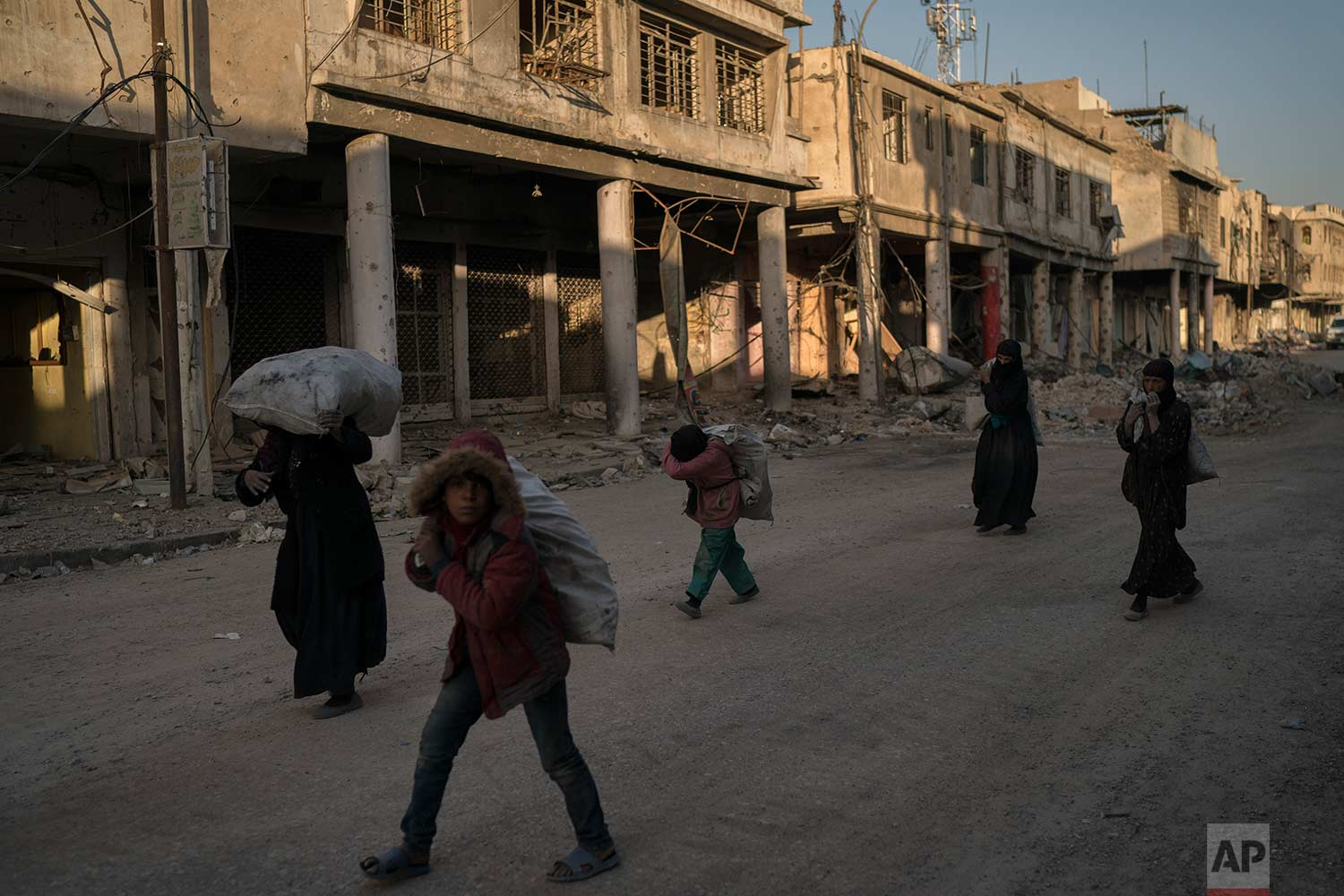 In this Nov. 16, 2017 photo, children and women carry metal scraps they collected from the rubble in the Old City of Mosul, Iraq. (AP Photo/Felipe Dana)