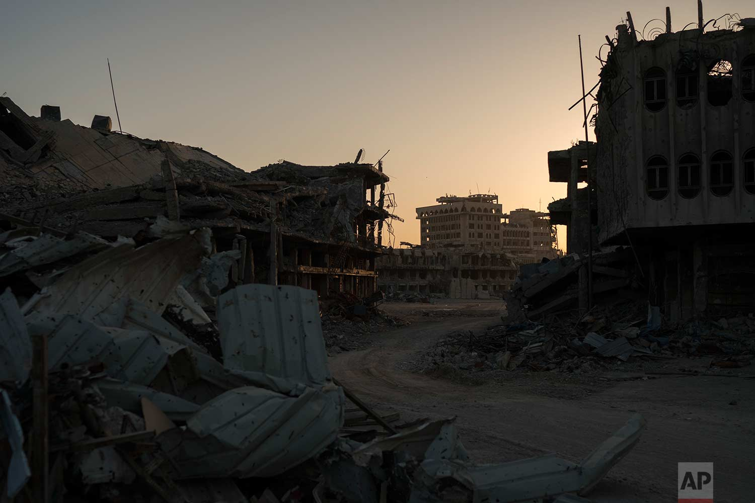 In this Nov. 16, 2017 photo, the sun sets behind damaged buildings in the Old City of Mosul, Iraq. (AP Photo/Felipe Dana)