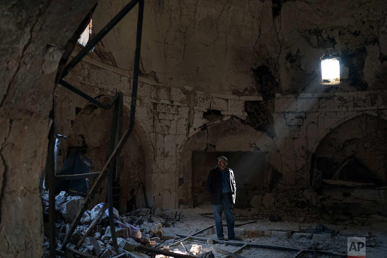 In this Nov. 14, 2017 photo, shop keeper Zyad Mohammed Ali, walks inside a damaged spa in the Old City of Mosul, Iraq. (AP Photo/Felipe Dana)