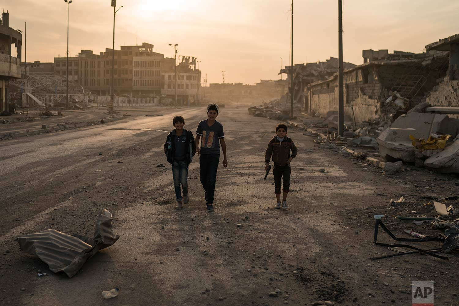 In this Nov. 15, 2017 photo, boys, one of them carrying a toy gun, walk on the empty streets of the Old City, in Mosul, Iraq.(AP Photo/Felipe Dana)