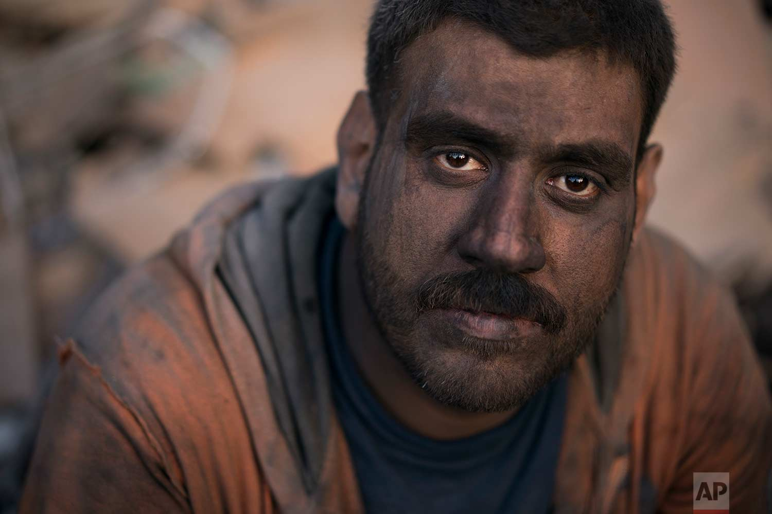 In this Nov. 15, 2017 photo, Ahmed Maha sits with his face covered in dirt after a day of work removing debris from a shop in the Old City of Mosul, Iraq. (AP Photo/Felipe Dana)