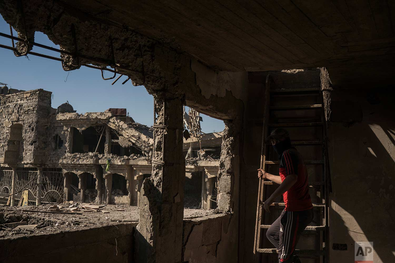 In this Nov. 14, 2017 photo, a construction worker climb the stairs of a destroyed shop in the Old City of Mosul, Iraq. (AP Photo/Felipe Dana)