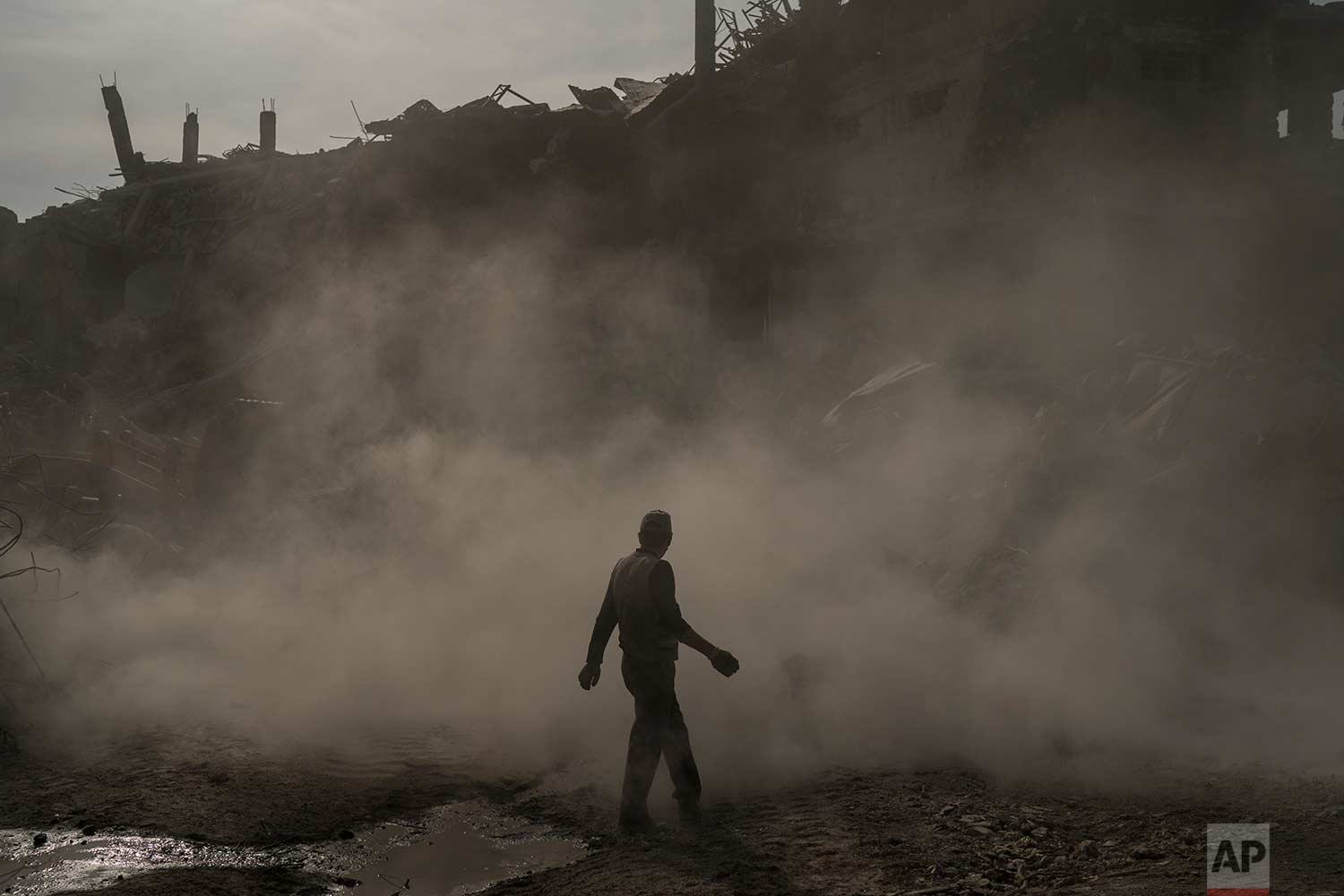 In this Nov. 18, 2017 photo, a construction worker walks amid a cloud of dust as a bulldozer removes debris from destroyed shops in the Old City of Mosul, Iraq. (AP Photo/Felipe Dana)