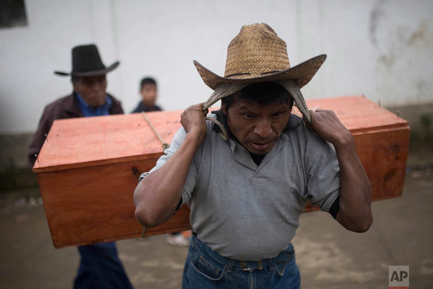 In this Nov. 30, 2017, an Ixil Mayan carries the remains of a civil war victim to a memorial for a mass burial in Santa Avelina, Guatemala. (AP Photo/Luis Soto)