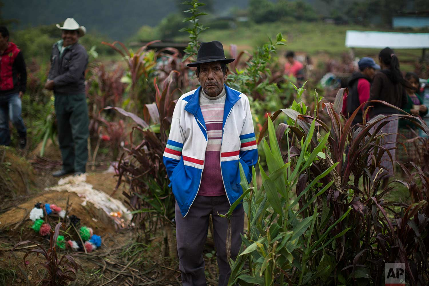 In this Nov. 30, 2017 photo, Tomas Cavinal Toma, 70, watches the burial of civil war victims at the cemetery in Santa Avelina, Guatemala. (AP Photo/Luis Soto)