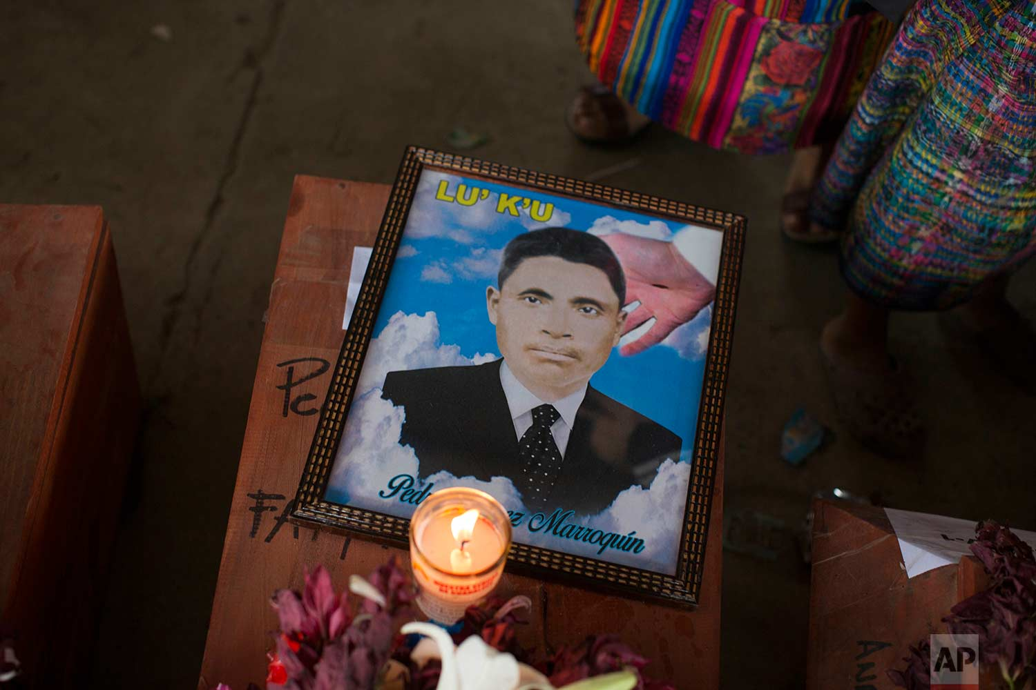 In this Nov. 30. 2017 photo, a portrait of Pedro Gomez Marroquin lays on his coffin during a memorial and burial of 171 people who died during the civil war in Santa Avelina, Guatemala. (AP Photo/Luis Soto)