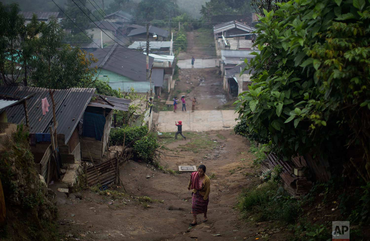 In this Nov. 30, 2017 photo, a woman walks up an unpaved road in the Ixil Mayan village of Santa Avelina, Guatemala. (AP Photo/Luis Soto)