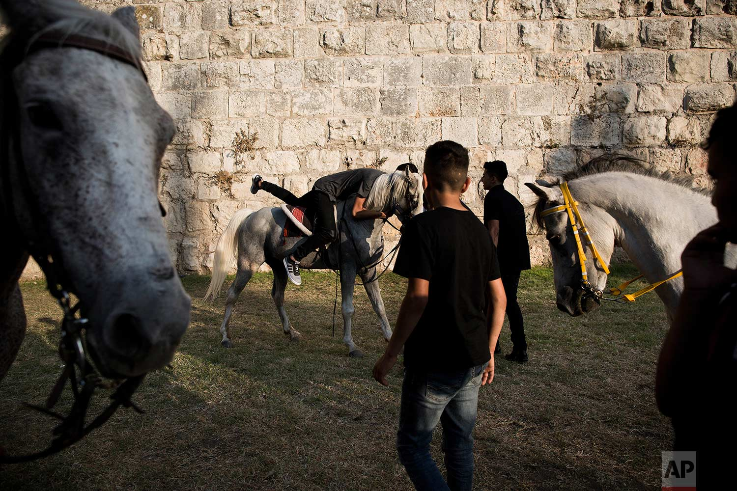 In this Tuesday, June 27, 2017 photo, Palestinians ride on horses during the Eid al-Fitr holiday outside Damascus Gate in Jerusalem. (AP Photo/Oded Balilty)