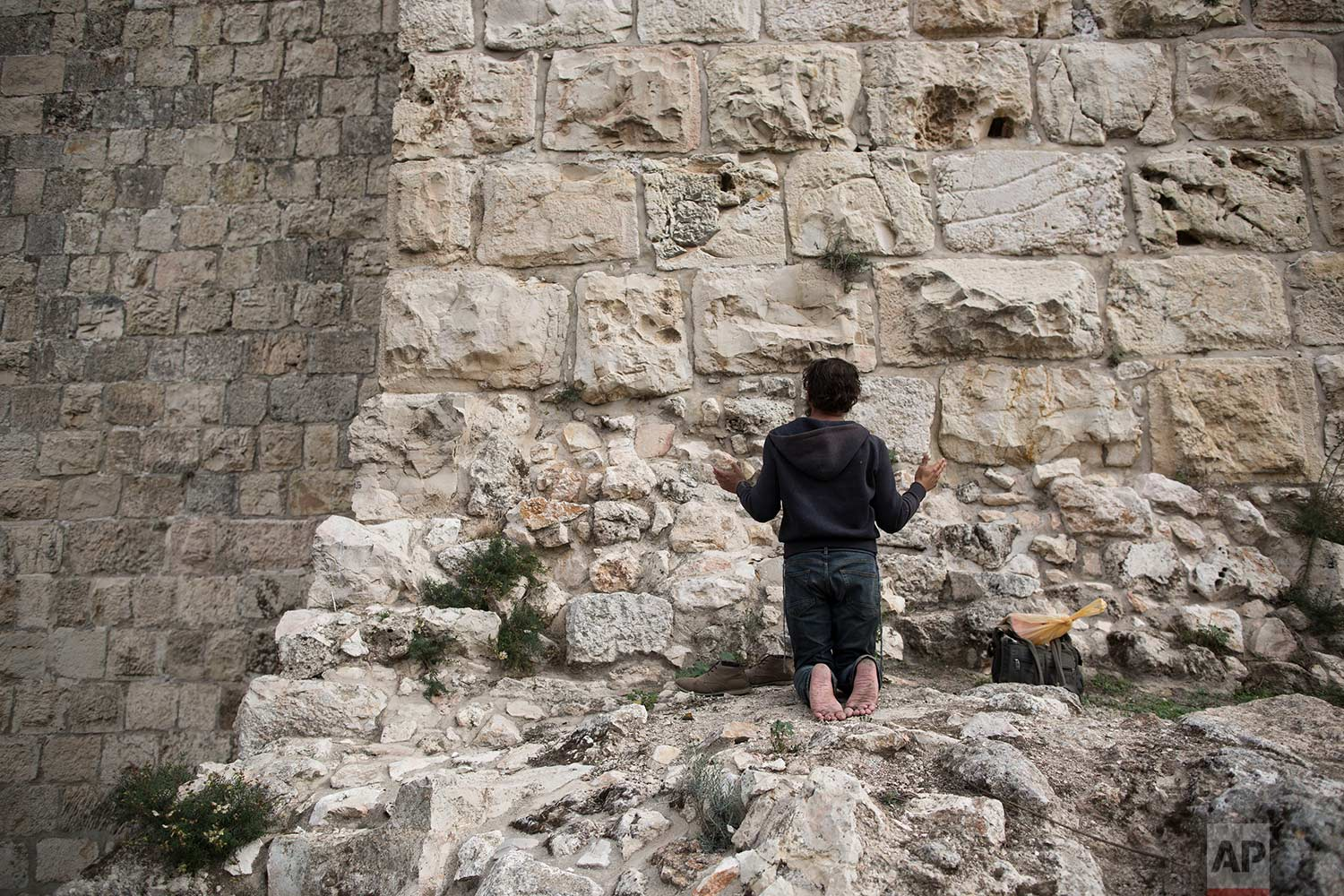 In this Tuesday, Dec. 19, 2017 photo, a man prays facing Jerusalem's Old City walls between Jaffa Gate and Zion Gate. (AP Photo/Oded Balilty)