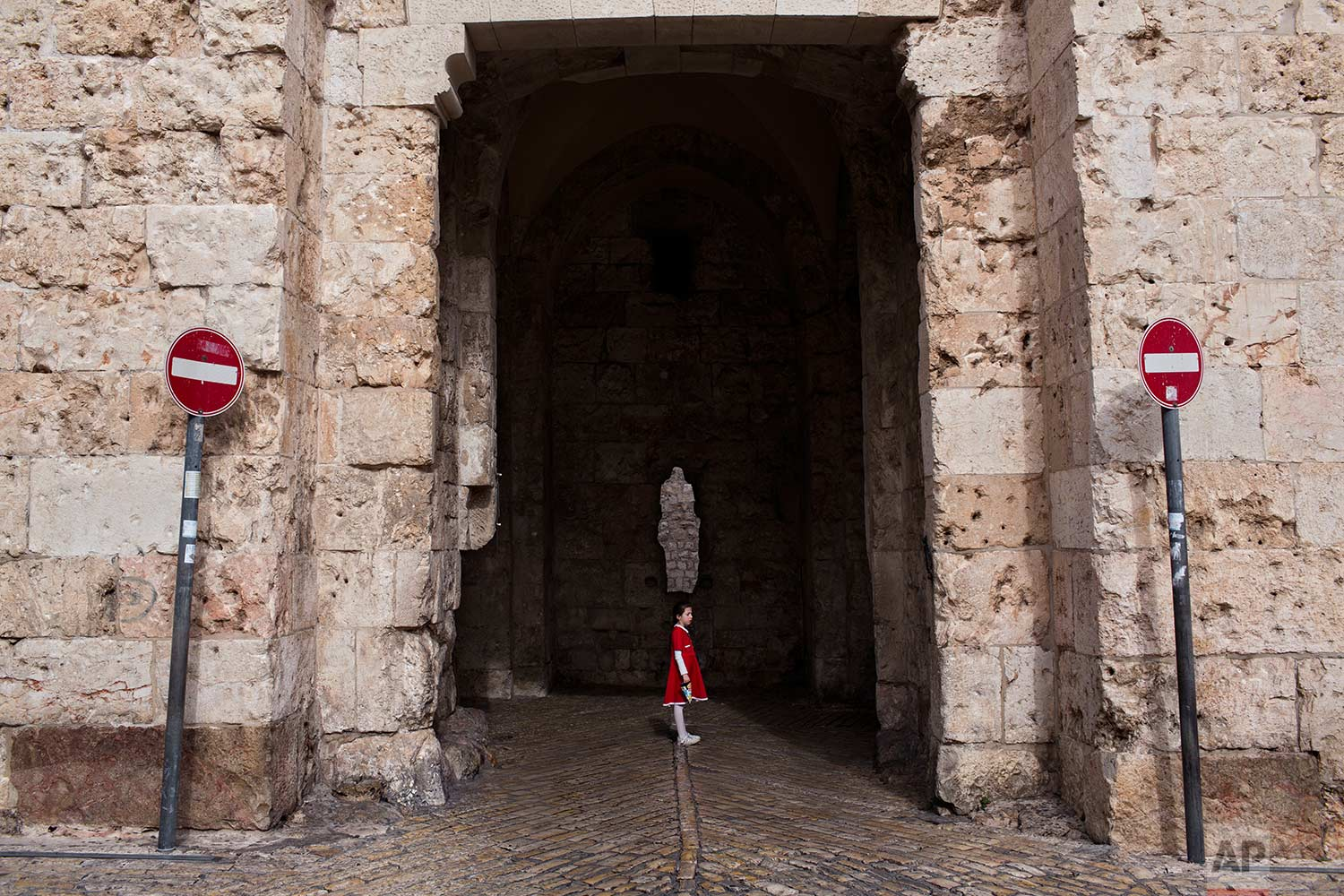 In this Tuesday, Dec. 19, 2017 photo, a young girl waits for her family to cross the Zion Gate in Jerusalem Old City. (AP Photo/Oded Balilty)