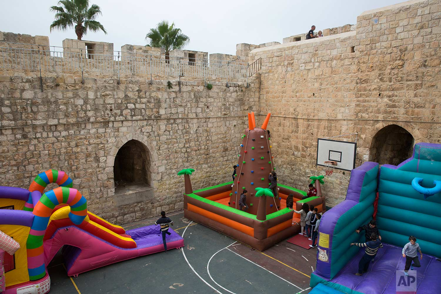 In this Thursday, Dec. 21, 2017 photo, Israeli Arab Christian school kids play on inflatables games in De La Salle school basketball yard surrounded by the Jerusalem's Old City walls next to the New Gate in Jerusalem Old City. (AP Photo/Oded Balilty)