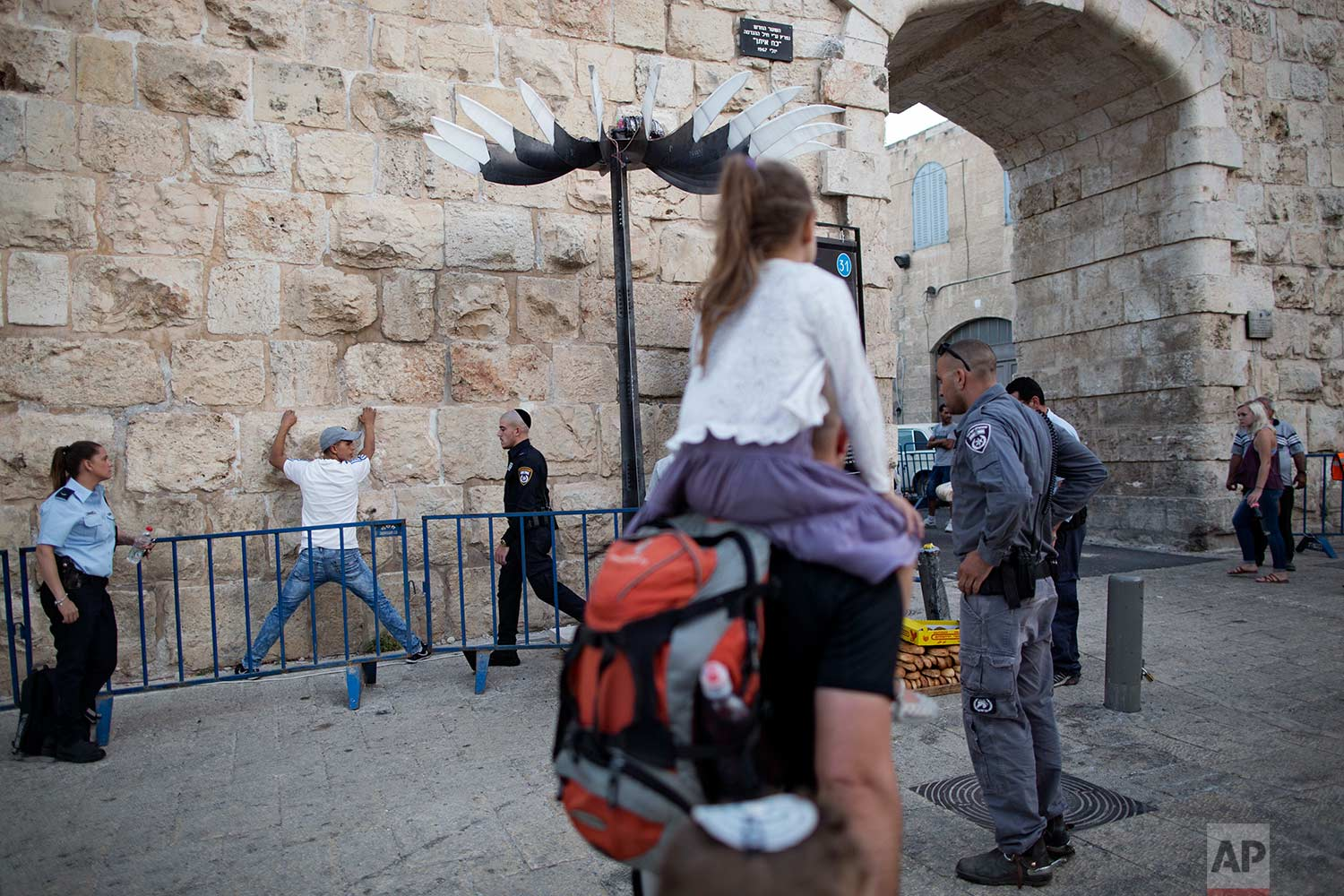 In this Thursday, July 6, 2017 photo, Israeli police officers search a Palestinian man next to the New Gate in Jerusalem Old City.  (AP Photo/Oded Balilty)