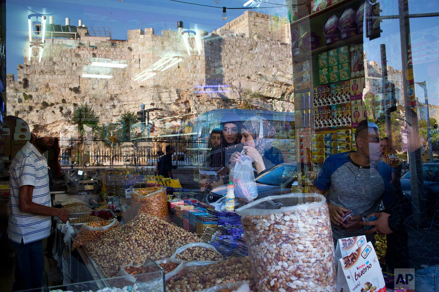 In this Saturday, Sept. 2, 2017 photo, people buy from a grocery store located between Damascus Gate and the Flowers Gate in Jerusalem's Old City. (AP Photo/Oded Balilty)