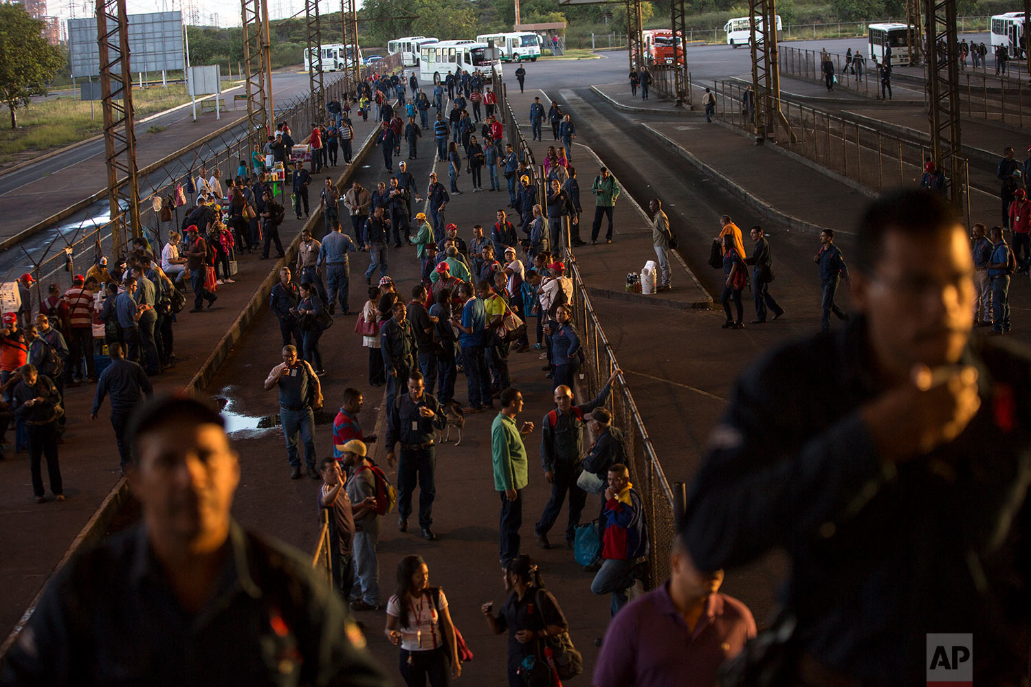 In this Nov. 7, 2017 photo, Sidor workers arrive for morning shift, in Ciudad Guayana, Bolivar state, Venezuela. Workers at the state-run factories quietly complain that they once proudly filled the ranks of Venezuela's middle class, taking their families out to eat and going on vacations. (AP Photo/Rodrigo Abd)
