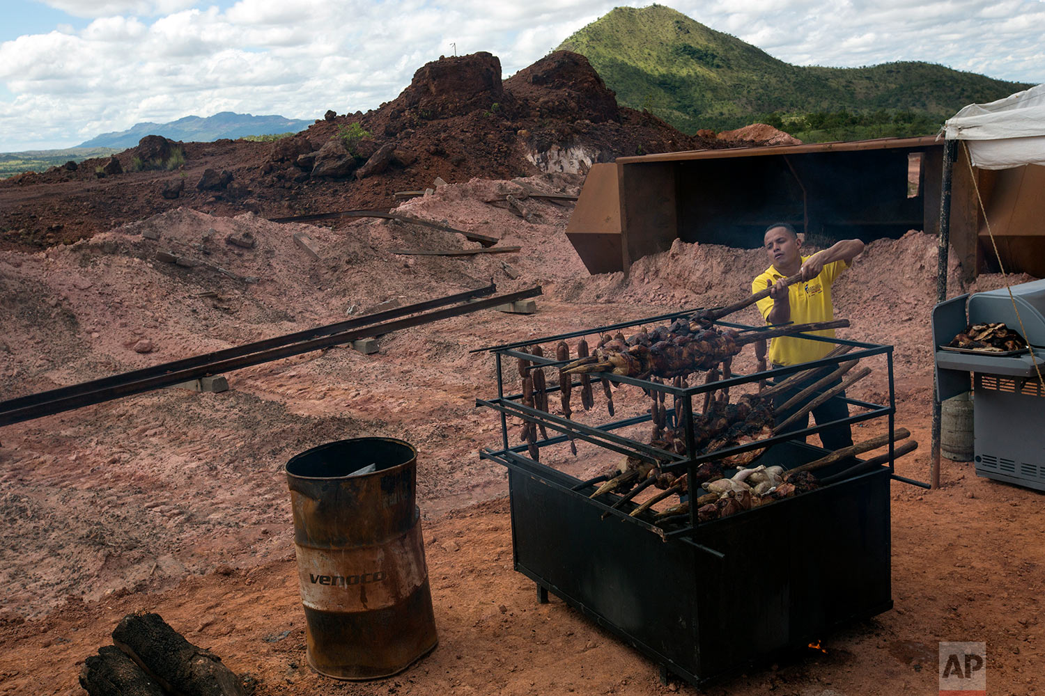 In this Nov. 2, 2017 photo, a Ferrominera Orinoco worker cooks sausages, pork and chicken to celebrate the completion of repairs on a set of damaged railroad tracks, in Ciudad Piar, Bolivar state, Venezuela. Some of the twisted rails and derailed train cars that used to carry iron ore can be seen in the background. (AP Photo/Rodrigo Abd)