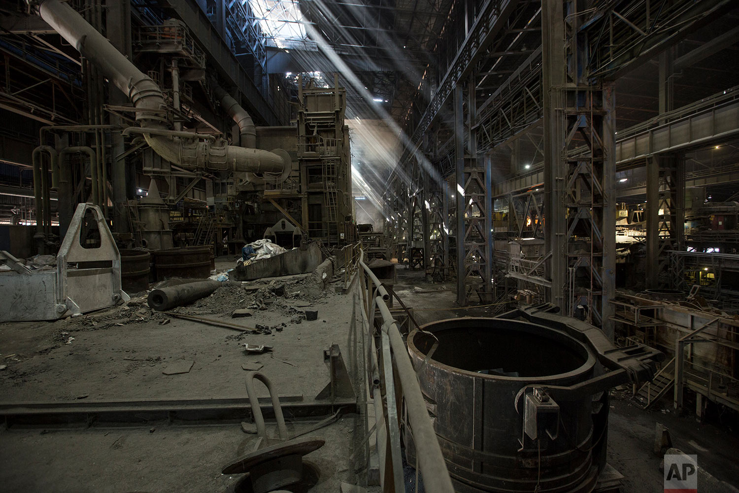 In this Nov. 7, 2017 photo, light rays enter through the windows of Sidor's Palanquilla steel plant, in Ciudad Guayana, Bolivar state, Venezuela. In 2008 President Hugo Chavez began putting these factories, then owned by conglomerates from Japan and Argentina, under the state's control. Output steadily eroded even before the oil price crash. (AP Photo/Rodrigo Abd)